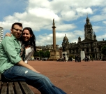 Self-timers can get you shots like this one: 1. Go to Glasgow. 2. Put the camera on the other side of the bench. 3. Push the button. 4. Jump behind your husband so it's not your thigh in the foreground. Also, this angel is way more interesting than the standard stand and smile variety.